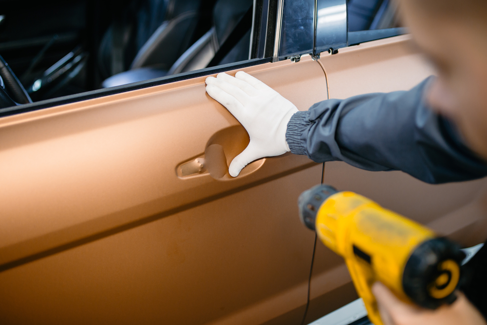 Folie-mit-Heißluftfön-erhitzen Auto selber folieren statt lackieren – Ratgeber, Wissenswertes und Tipps
